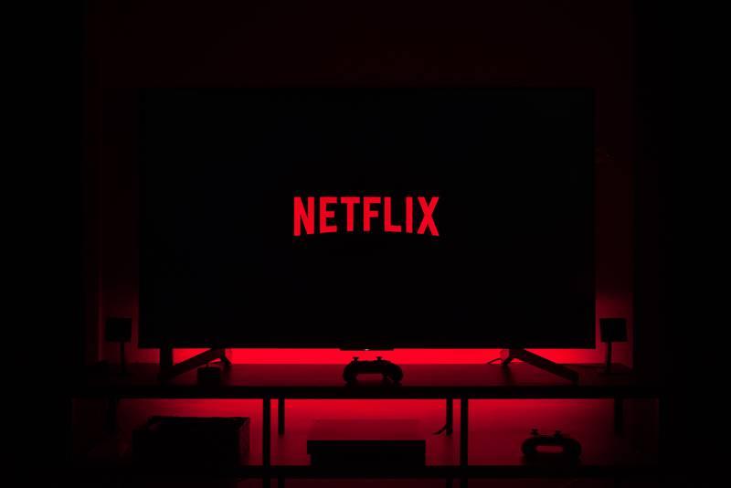 Televisão em sala escura exibindo logo da Netflix